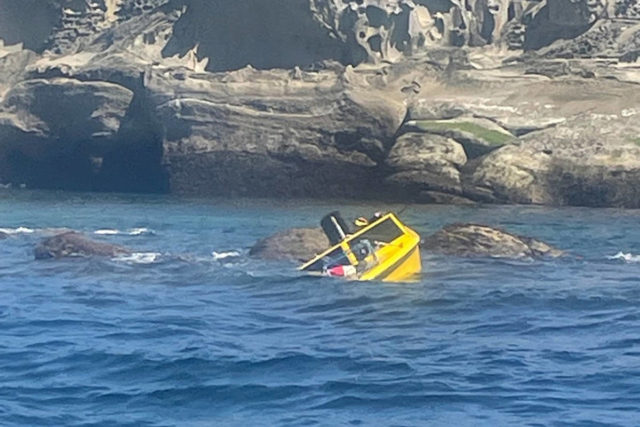 A small, yellow powerboat sinking
