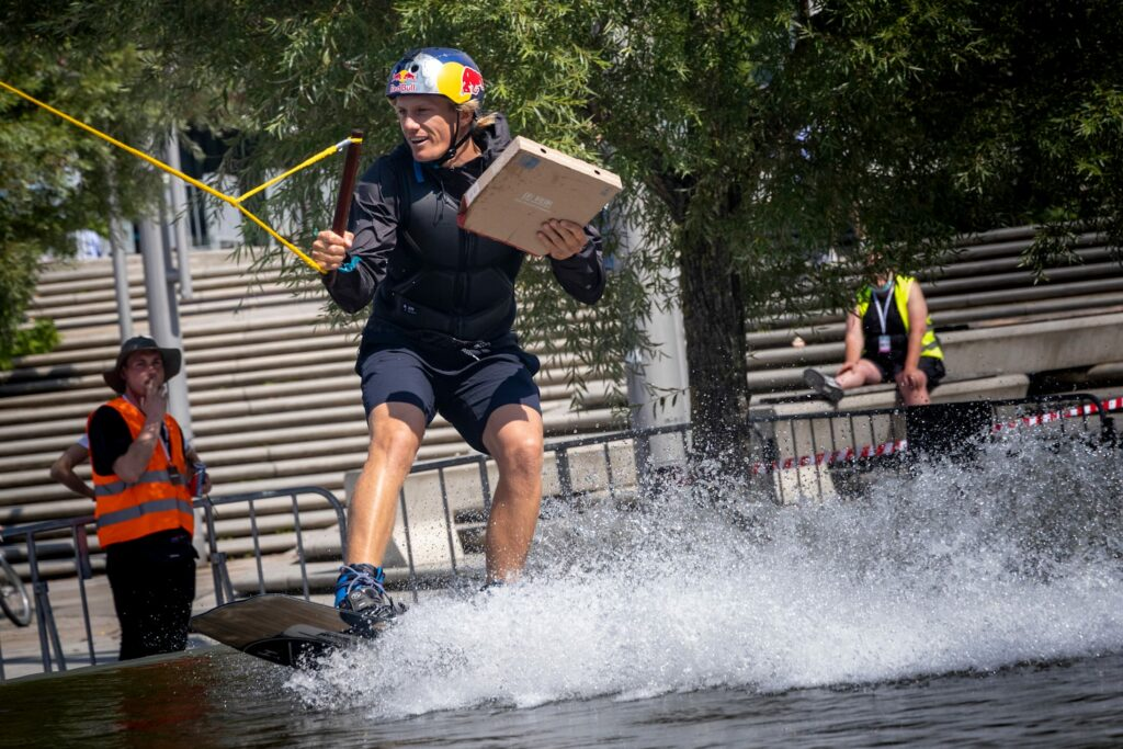 Domenic Guhrs wakeboarding whilst holding a pizza