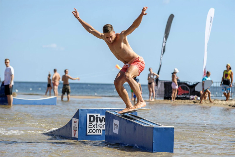 A person skimboarding on a rail/ramp.