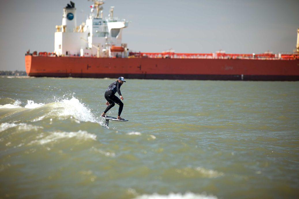 A person wake-foiling the waves from a massive cargo ship.