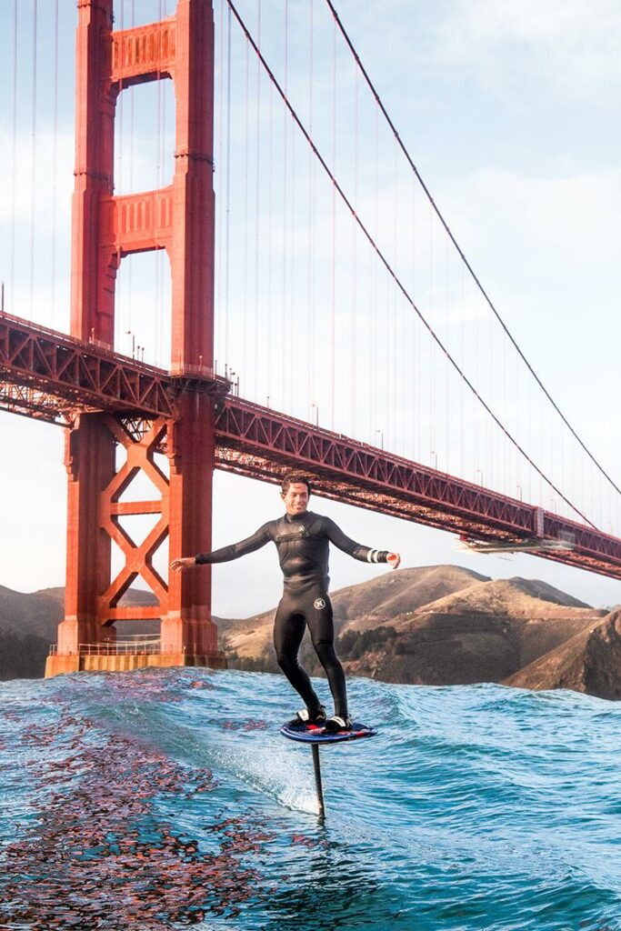 Kai Lenny foiling on a board with the Golden Gate Bridge behind him.