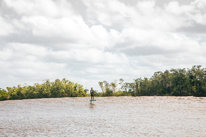 Vinnicius Martins foil surfing a wave with the Amazon in the background.