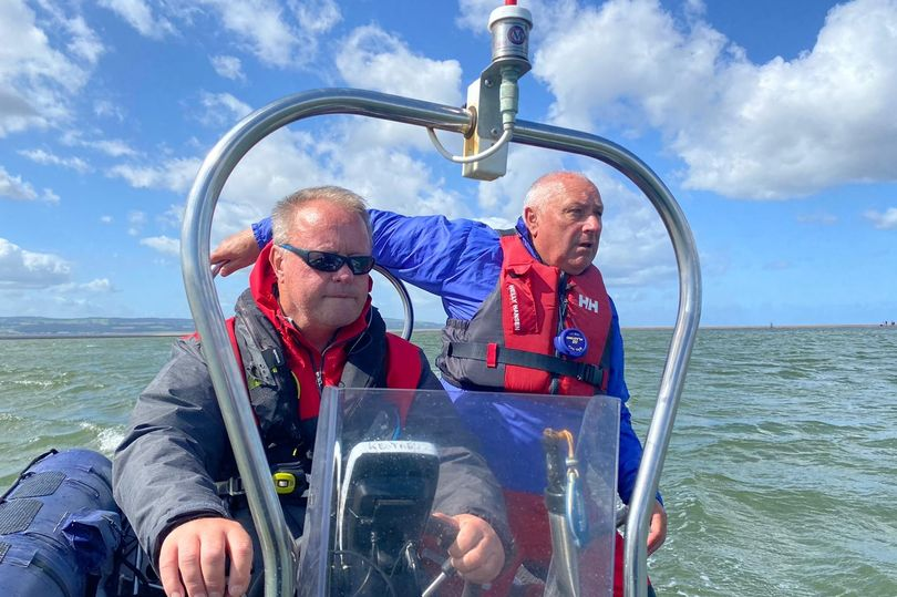 Man driving a powerboat with another man standing next to him.