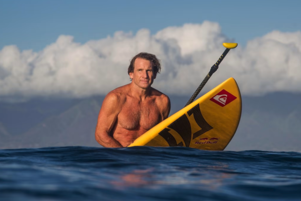 Robby Naish sitting on a paddle board with clouds and a volcano in the bacdrop.