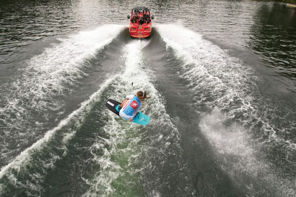 Aerial shot of a wakeboarder behind a speed boat.