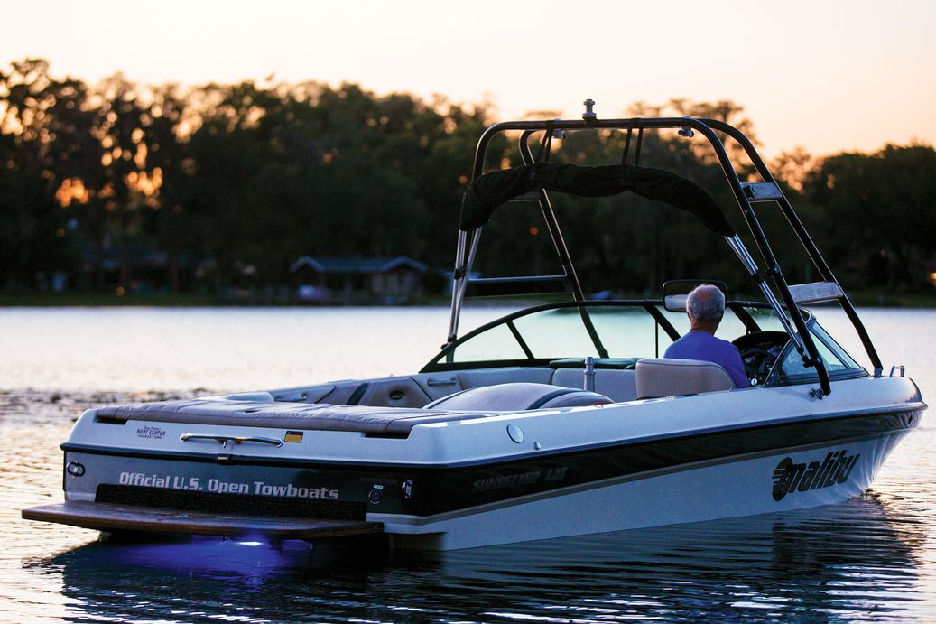 A wakeboarding boat on flat water at sunset.