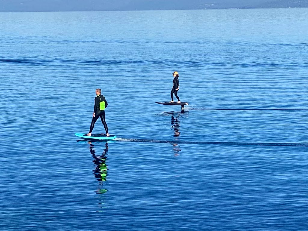 Two people foiling on flat water.