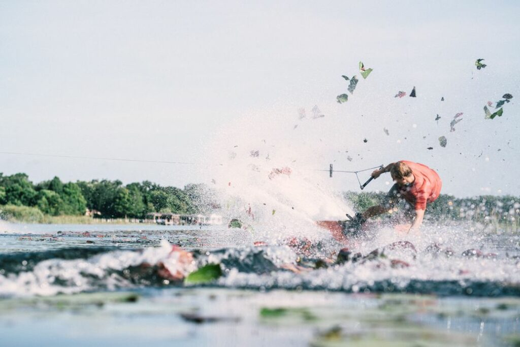 A person wakeboarder, creating a lot of splash and lily pads flying in the background.