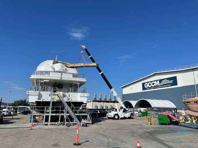 60-metre motor yacht, Oceana. A crane dropping stuff onto the top deck of the boat.