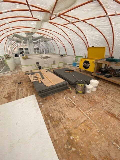 Wooden decking before floor has been put down. Plastic temporary roof. Work gear everywhere.