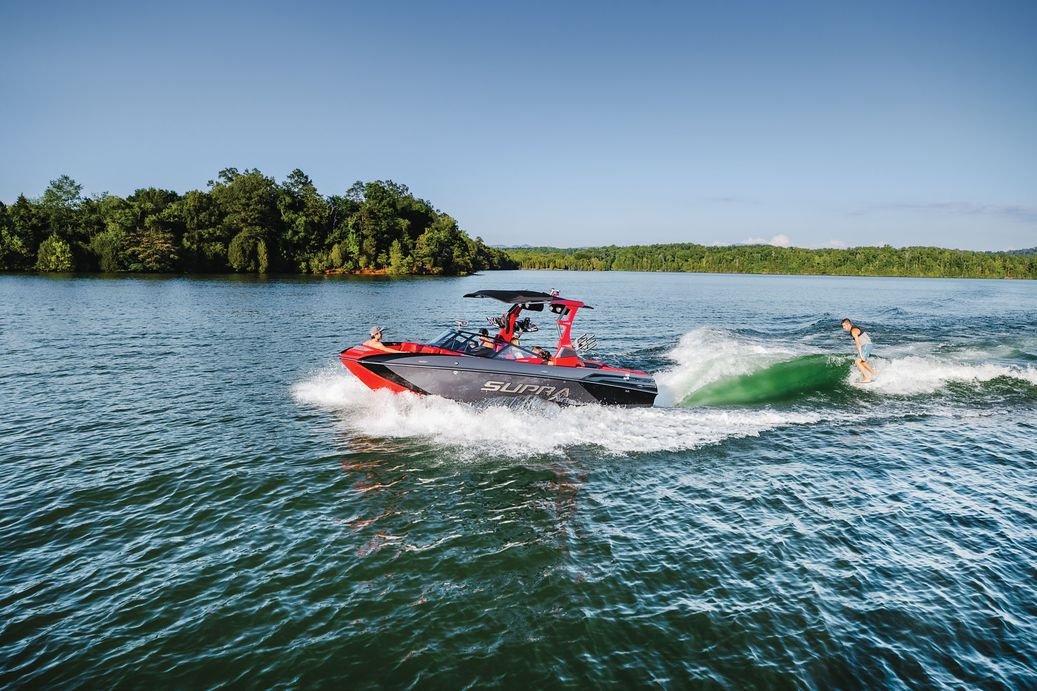 Supra boat driving with a wakeboarder towed behind.