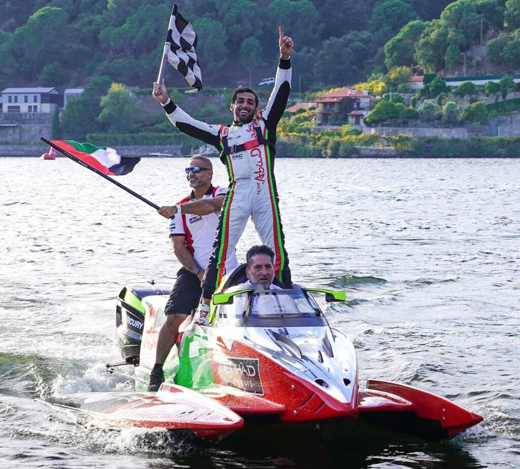 Edgaras Riabko celebrating his win with team driving in on powerboat.